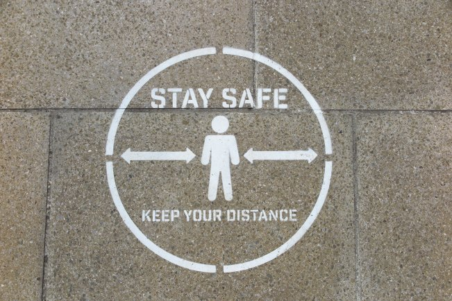 Stay Safe Keep Your Distance social distancing marker on pavement